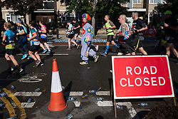 © Licensed to London News Pictures. 03/10/2021. London, UK. A runner dressed as a clown passes through Greenwich as part of the 2021 London Marathon.This London Marathon will be the first full scale staging of the race in more than two years due to the Coronavirus Pandemic.  Photo credit: George Cracknell Wright/LNP