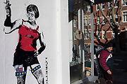 Satirical street art depicting Prime Minister Theresa May wearing risque clothes and smoking a cigarette in London, England, United Kingdom.