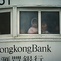 China, Hong Kong, Mother and child peer from street trolley window
