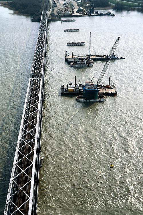 Nederland, Hollandsch Diep, 08-03-2002; rivier met spoorbrug - Moerdijkbrug, HSL komt rechts naast bestaande spoorbrug te lopen (Westelijk); er wordt gewerkt aan pijlers in het water voor de nieuwe HSL brug (elipsvormige fundering); aan de horizon het Zuidelijke bruggenhoofd / bouwput bouwterrein; infrastructuur verkeer en vervoer spoor mobiliteit transport brug tegenlicht water landschap (zie ook andere (lucht)foto's Hollandsch Diep);<br /> luchtfoto (toeslag), aerial photo (additional fee)<br /> foto /photo Siebe Swart