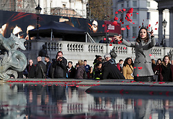 Laura Wright throws poppies in the fountain during an event in London's Trafalgar Square to mark Armistice Day.