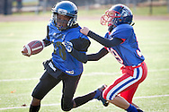 Newburgh, New York - A Middletown runner tries to break away from a Goshen defender in the Orange County Youth Football League Division II Super Bowl at Newburgh Free Academy on Nov. 22, 2014.