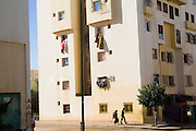 A Moroccan couple walks along a sidewalk below a modern apartment building in a modern middle-class suburb of Meknes, Morocco. Clothes hangs to dry in the sun from apartment windows.