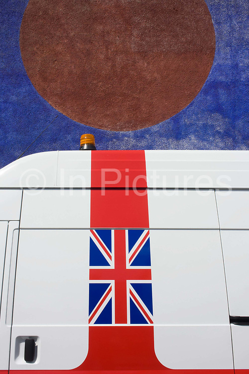 Union jack flag on the side of a white van in south London. As a metaphor for the working man in Britain, the white van shows Britain's national flag with a door handle and hazard light on its roof. Above is a mural onn the wall of a nearby house.