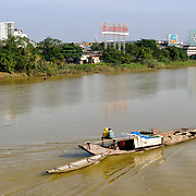 A boat carrying dredged sand goes up the Perfume River in Hue, Vietnam. In the background is the shore, with large advertising signs that are illuminated at night.