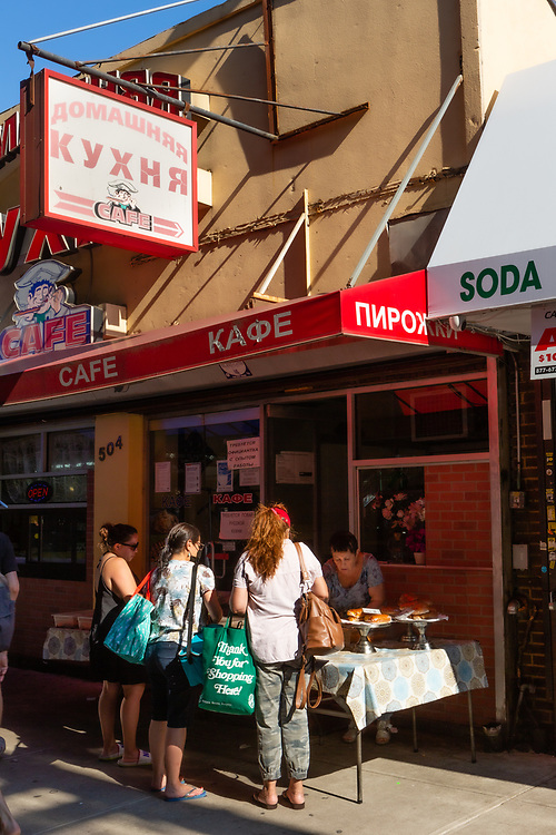 Serving pastries on the sidewalk at the Home Made Cooking Cafe (in Russian omshnyaya Kukhnya) on Brooklyn's Brighton Beach Avenue.