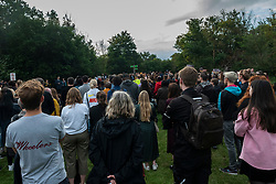 © Licensed to London News Pictures. 03/08/2021. LONDON, UK.  People attend a vigil at Barn Hill Pond, Fryent Country Park near Wembley to remember the lives of sisters Bibaa Henry and Nicole Smallman, on what would have been Nicole's 29th birthday.  The sisters were murdered in the park in June 2020 whilst celebrating Bibbaa's birthday.  Reclaim These Streets have worked with former Archdeacon of Southend, the Ven. Wilhelmina (Mina) Smallman, the late sisters' mother, to organise the vigil and attendees were encouraged to wear green and purple, the sisters' favourite colours, or light a candle.  Photo credit: Stephen Chung/LNP