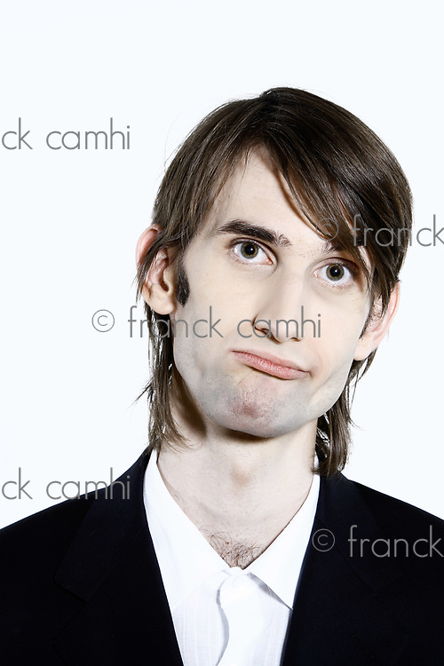 studio shot portrait of a young funny expressive thin and tall man on isolated background geting bored
