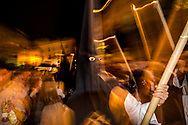 """A Nazareno of La Soledad Brotherhood in the night of Holy Saturday walks among the crowd populating a street in Sevilla. """"Nazarenos"""", dressed with a black """"capirote"""", the peculiar conical hat, and a white tunic  make penance carrying along the procession either long (and heavy) candles, chandeliers or wooden crosses."""
