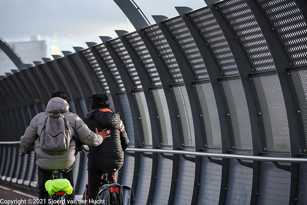 Cyclist gives other cyclist a helping hand.   Fietser geeft andere fietser een duwtje in de rug.