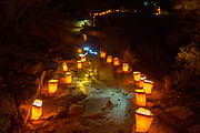 Small paper lanterns known as luminarias light the pathway around the canyon at Spruce Tree House cliff dwellings as the blurred flashlight trails of tourists snake past during open house December 10, 2015 in Mesa Verde National Park, Colorado.