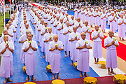 19 JULY 2014 - KHLONG LUANG, PATHUM THANI, THAILAND: Men who will be ordained as Buddhist monks gather in front of the ordination hall at Wat Phra Dhammakaya. Seventy-seven men from 18 countries were ordained as Buddhist monks and novices at Wat Phra Dhammakaya, a Buddhist temple  north of Bangkok, Saturday. It is the center of the Dhammakaya Movement, a Buddhist sect founded in the 1970s and led by Phra Dhammachayo (Phrathepyanmahamuni). It is the largest temple in Thailand. The Dhammakaya sect has an active outreach program that attracts visitors from around the world.    PHOTO BY JACK KURTZ