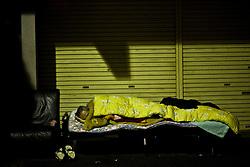 A man sleeps outside in Kamagasaki, Japan.