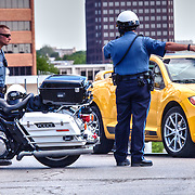 Kansas City police officers directing car traffic being re-routed around a marathon, 51st and Main Streets, Kansas City, Missouri.