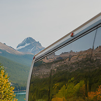 Mount Noyes and the Canadian Rockies reflect in the windows of a tour bus in Banff National Park, Alberta, Canada.