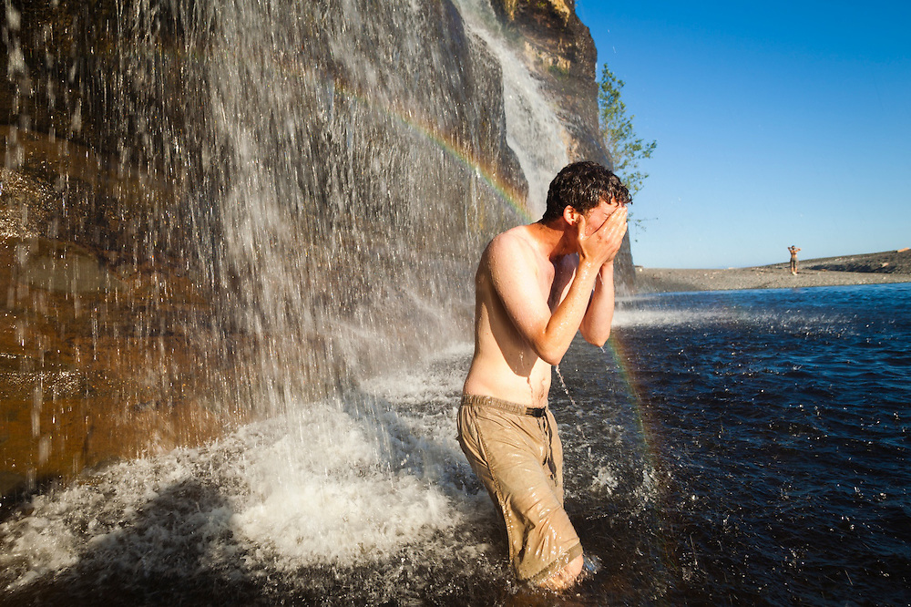 Zach Podell-Eberhardt washes himself under the spray of Tsusiat Falls, West Coast Trail, British Columbia, Canada.