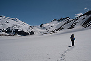 A backpacker crosses a snowfield on the way to Mageik Lakes in Alaska's Valley of Ten Thousand Smokes
