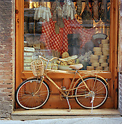 A bicycle stood in fron of a shop window in Siena, Tuscany, Italy