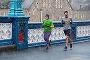 Two joggers smile as they run across Tower Bridge during a heavy snow shower on December 10th, 2017. Much of the UK has been hit by heavy snow and The Met Office have issued a yellow weather warning for snow and ice across most of the United Kingdom.