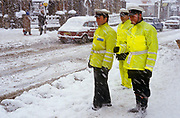 Standing on the roadside are three British traffic policemen. It is snowing in the depths of winter and the three officers are watching on-coming traffic as it negotiates safe routes downhill in South London. Wearing yellow jackets of the early 1990s we see the traces of snow that fell across the scene in diagonal blurs. Cars of the era drive along roads that have succumbed to the snowfall, seemingly unsalted or treated with anti-snow grit. In the background a couple walk carefully on hazardous pavements.