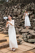 A Chinese women take a selfie photo from her phone dressed in white bridal dresses standing by the ancient ruins of Angkor Thom, Siem Reap Province, Cambodia, South East Asia. A second woman, also dressed as a bride, stands on the stone wall with a DSLR camera.  photo by Andrew Aitchison / In pictures via Getty Images