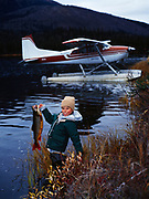Bush pilot's son, Tyler Klaes, proudly displays a Lake Trout in spawning colors just caught in a small lake near the Alatna River on the south side of the Brooks Range, Alaska.