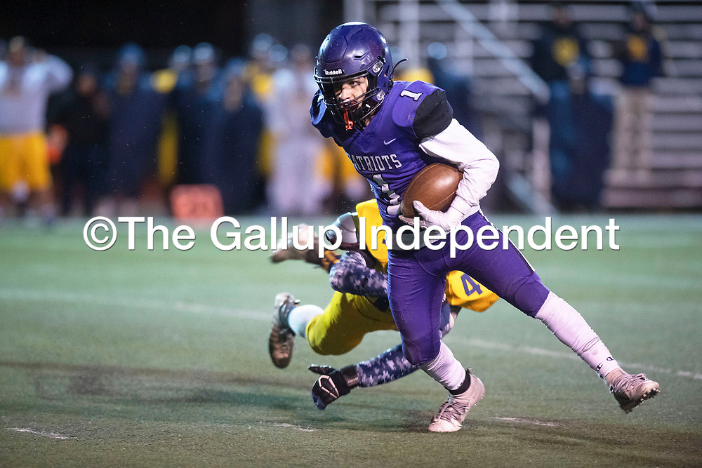 Miyamura Patriots' Drake Guerrero (1) breaks a tackle by Highland Hornets' Philip Van Dalen (44) on a touchdown run Friday night at Angelo DiPaolo Memorial Stadium in Gallup.
