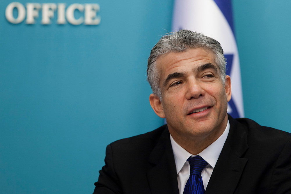 Israel's Minister of Finance Yair Lapid smiles during a press conference in which the Israeli government  presented a new planned sea ports reform in Israel, at the Prime Minister's Office in Jerusalem, on July 3, 2013. The Israeli government initiated a tender for two new private ports to operate beside existing government-owned ports in Haifa and Ashdod in a bid to raise competition, break the monopoly in the current system and lower the costs of good in Israel.