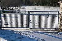 Snow covered field and gate to kilbogget park in Dublin Ireland