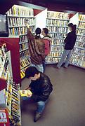 Nederland, Nijmegen, 15-5-1992Jongeren kijken in een videotheek naar banden met films. De video vond haar einde toen de dvd opkwam, medio jaren 90 . In de jaren 80 van de vorige eeuw nam het aantal videotheken sterk toe dankzij de komst van de videorecorder. De videotheken boden verschillende videoformaten aan (Betamax, VHS, Video 2000). In de jaren 90 richtten de videotheken zich meer op VHS en cd. In het begin van 21e eeuw verhuren de bedrijven alleen dvd's aan de klanten.Foto: Flip Franssen