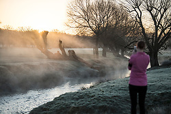 © Licensed to London News Pictures. 16/12/2017. London, UK. A runner stops to take a picture of a frost and mist covered landscape in Richmond Park. Parts of the UK are experiencing freezing temperatures today with snow expected in parts. London, UK. Photo credit: Ben Cawthra/LNP