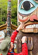 USA, Alaska,Ketchikan, A man examines the textures of a totem at Totem Bight State Historic Park in Ketchikan.MR