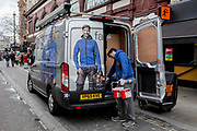 An employee with Fallon & Co. wearing identical work top uniform as the male on the rear of his companys parked van, gathers tols and materials including Soldalit, an exteriors water repellent paint, on 17th February 2020, in London, England. Fallon & Co is  a privately owned business with over 25 years experience servicing clients in the Domestic, Commercial & Industrial sectors.
