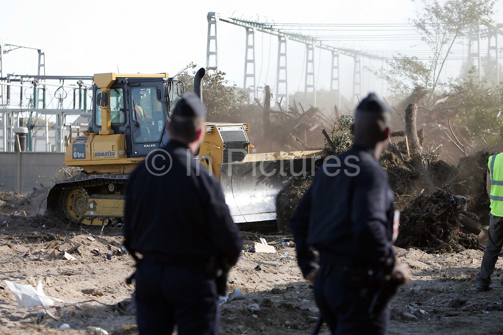 French Policemen look on as diggers crush the last remnants of the Afghan migrants camp in Calais, France, September 24, 2009. The migrants had been moved by Police the previous day from their makeshift camp in the outskirts of Calais known as 'The Jungle'. For many 'The Jungle' was their last stop before attempting to illeagally cross the English Channel to the UK.    Picture by Paul Hackett/ Corbis