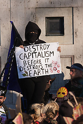 London, March 7th 2015. Following the Climate march through London, masked anarchists and environmental activists clash with police following a breakaway protest at Shell House. PICTURED: A protester demands that capitalism is destroyed.