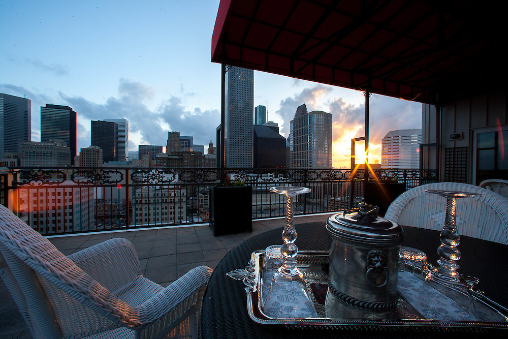 Houston, Texas skyline viewed from residential balcony of luxury high-rise at sunset with romantic tray of elegant wine glasses and ice bucket.