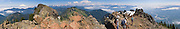 From atop Sauk Mountain can be seen the North Cascades from Mount Baker southwards to Glacier Peak and Three Fingers. (Panorama stitched from 11 images). On the right, far below the hikers is the Sauk River at its confluence with the Skagit River, Washington, USA.