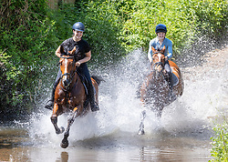 Licensed to London News Pictures. 03/06/2021. London, UK. Horse riders Calia Logan 17 and her friend Sophie Hamilton 26 along with their trusted Dutch Warm Bloods cool off in a water splash in Barkham Surrey as the fine June weather continues. The Met Office have forecast very warm weather for the South East and London with temperatures predicted to hit up to 24c this week. Photo credit: Alex Lentati/LNP