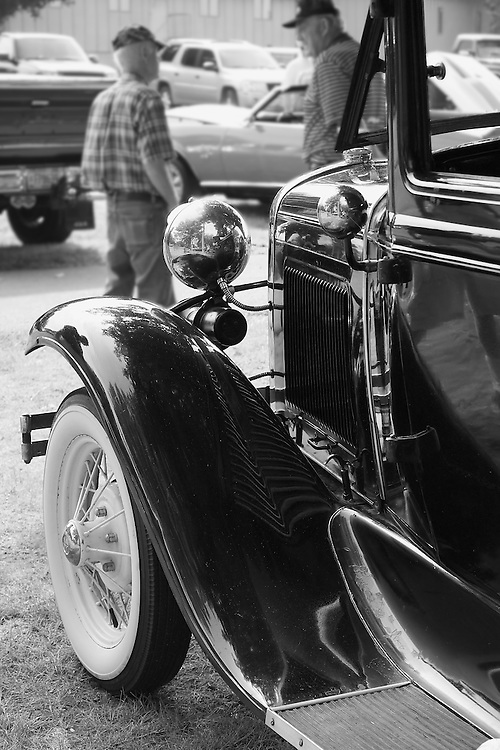 Two old men talking by an antique car, black and white.