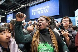 11 December 2019, Madrid, Spain: A woman raises her hand into the air while calling out for climate justice, as hundreds of civil society and other actors hold an unauthorized protest outside the plenary hall of COP25 in Madrid, to draw attention to the failures of the climate talks and to call on rich countries to step up and pay up for real solutions, and to highlight the threat of loopholes, false solutions like carbon markets, and the need for those who caused the climate crisis to pay up for loss and damage while respecting human rights.