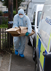 © licensed to London News Pictures. Braintree, UK  06/06/2011. A forensics officer carrying evidence bags large enough to carry a shotgun out of 40 Bartram Avenue in Braintree, Essex today (06/06/2011) where the bodies of a woman and a child were found following a shooting. Officers were called to reports of a firearms incident in the early hours of the morning. Photo credit should read Ben Cawthra/LNP