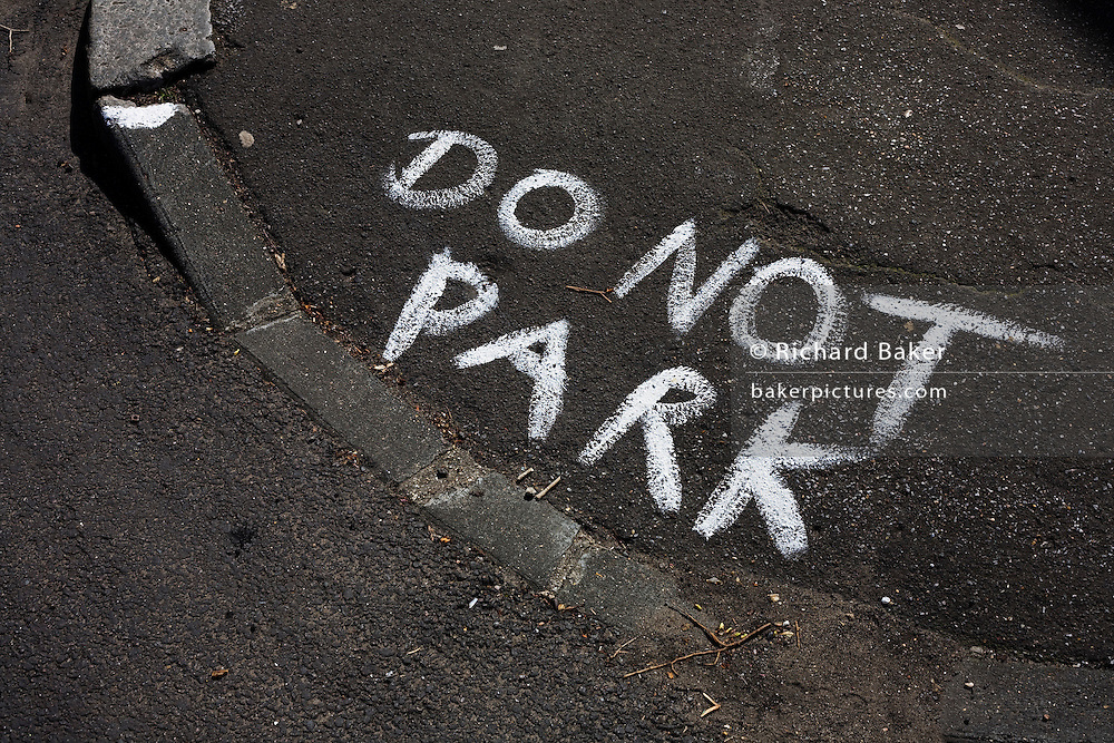 The words Do Not Park have been painted roughly on a kerbside street corner in the London borough of Lambeth, England.