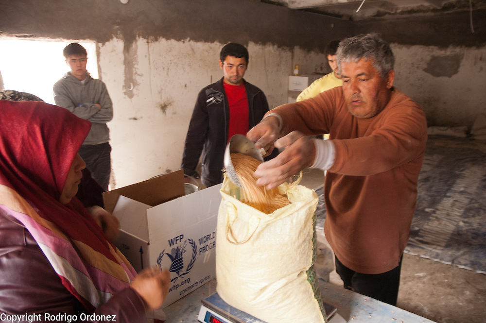 Save the Children staff prepares rations during a distribution of food donated by the World Food Programme (WFP) in the neighborhood of Kizil Kishtak in Osh, Kyrgyzstan.