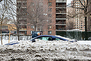 A blue car, parked on the street outside a tower block of flats in Upper West Side, New York City,  New York, United States of America, covered in snow after the snowstorm in January 2016. The snowstorm brought more than 2 feet of snow in many areas, which broke many records.