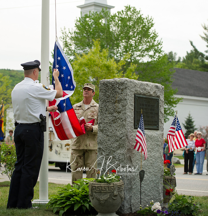 Gilford Police Chief Anthony Bean Burpee and Lt. Col. Kurt Webber (retired) raise the American flag during the Memorial Day service in Gilford Village Monday morning.  (Karen Bobotas/for the Laconia Daily Sun)