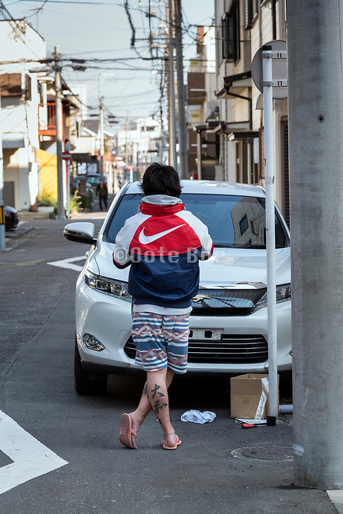 man working on his car with large tattoo on his calf muscle Yokosuka Japan