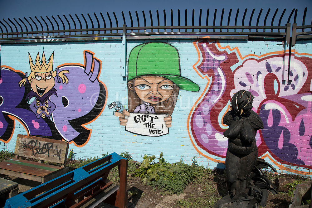 Street art by various artists in the Nomadic Community Garden in Shoreditch, East London, United Kingdom. This area was once waste ground, and has been taken over by people, where they mix art and gardening in a positive space. Nomadic Community Gardens NCG is a not for profit organisation based in Shoreditch, East London. We are dedicated to transforming disused spaces into urban gardens where people can grow their own produce, create art, share skills, and discover what it means to build their own community from the bottom up. Street art in the East End of London is an ever changing visual enigma, as the artworks constantly change, as councils clean some walls or new works go up in place of others. While some consider this vandalism or graffiti, these artworks are very popular among local people and visitors alike, as a sense of poignancy remains in the work, many of which have subtle messages.