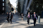 At the base of the Leadenhall Building, city workers walk in the sunshine surrounded by new high rise modern architecture in the City of London, England, United Kingdom. As Londons financial district grows in height, the classical buildings are being dwarfed by the towers of glass.