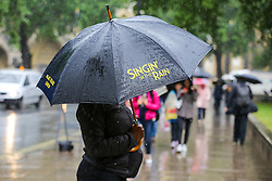 "© Licensed to London News Pictures. 10/06/2019. London, UK. A woman shelters from the rain beneath an umbrella, ""Singing' in the Rain"" written on it, as rain falls in the capital. The Met Office has issued an amber warning for more rain, covering London and parts of southeast England later today.  Photo credit: Dinendra Haria/LNP"