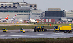 © Licensed to London News Pictures. 29/02/2016. Gatwick, UK. Tractors carrying cleaning equipment clean the runway at Gatwick Airport in West Sussex, where the main runway has been closed due to a spillage. Photo credit: Peter Macdiarmid/LNP